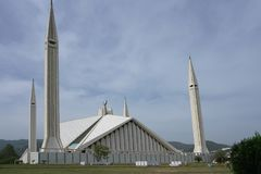Islamabad, Pakistan - April 15 2018 : Pakistani resting around Faisal Mosque under blue sky in Islamabad royalty free stock photography