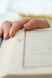 Islamic. Female fingers over Holy Koran page Stock Photography