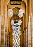 Islamic Architecture. A hallway with columns and lamps lead to a carved panel typical of islamic architecture Royalty Free Stock Image
