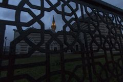 A mosque and its sodium lamp illuminated minaret seen from a forged iron fence with islamic geometric patterns in dusk. royalty free stock image