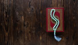 Islamic book Koran with rosary beads on wooden background. Islamic concept with copy space. Quran with rosary on wooden background stock images
