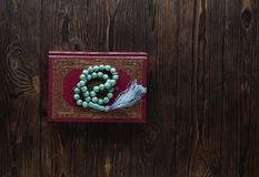 Islamic book Koran with rosary beads on wooden background. Islamic concept with copy space. Quran with rosary on wooden background stock photography
