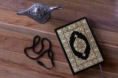Islamic book Quran on the wodden board with a rosary and aladdin lamp -Ramadan /Eid Concept. Holy islamic book Quran on the wodden background with a rosary and stock photography