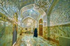 Islamic cleric in Imam Zadeh Jafar Shrine, Yazd, Iran. YAZD, IRAN - OCTOBER 18, 2017: Islamic cleric mullah walks the scenic mirror coridor of Imam Zadeh Jafar royalty free stock image