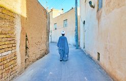 In old Kashan, Iran. Islamic cleric mullah walks the old narrow curved street of the city with high wall-fences, Kashan, Iran royalty free stock image
