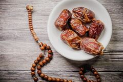 Tasbih rosary beads and Tamar Dates  against wooden background