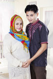 Islamic couple standing in bedroom. Portrait of islamic pregnant women and her husband standing in the bedroom Stock Image