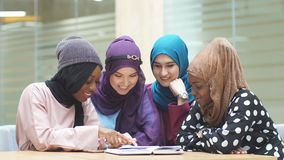 Islamic female travel blogger sharing info from smartphone with her followers. While sitting in group of four in hotel lobby stock footage