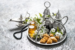 Islamic holidays food with decoration. Ramadan kareem. Eid mubarak. Oriental hospitality concept. Tea glasses and pot, traditional delight baklava stock image