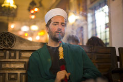 Islamic man with traditional dress smoking shisha, drinking tea Stock Photos