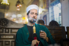 Islamic man with traditional dress smoking shisha, drinking tea Stock Photo