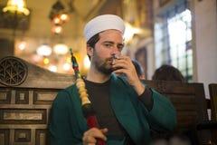 Islamic man with traditional dress smoking shisha, drinking tea Stock Photography