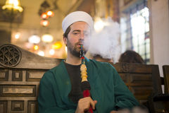 Islamic man with traditional dress smoking shisha, drinking tea Stock Images