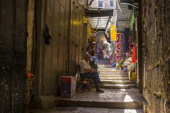 An Islamic man waiting for custom outside his small shop in a narrow street royalty free stock images