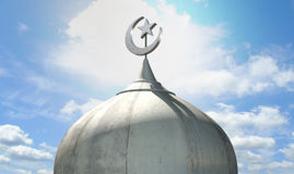 Islamic Minaret. A closeup of the top of a mosque minaret with a cupola dome and an islamic crescent moon and star on a blue sky background Stock Photo