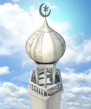Islamic Minaret. A mosque minaret with a cupola dome and an islamic crescent moon and star on a blue sky background Royalty Free Stock Images