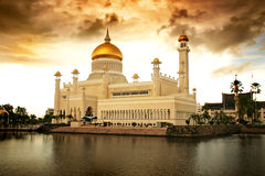 Islamic Mosque. Over the water with golden clouds royalty free stock photo