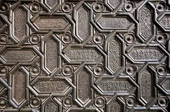 Islamic patterns and Arabic calligraphy in metal surface of door the 16th centure Seville Cathedral, Spain. Motifs in artworks of Andalusia royalty free stock photo