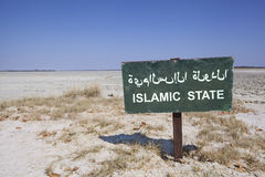 Islamic state. Green sign in the desert with the words islamic state in english and arabic letters. Political concept concerning terrorism and the war in Syria Stock Photography