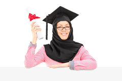 Islamic student with mortarboard and veil holding diploma behind. Female Islamic student with mortarboard and veil holding diploma behind blank panel isolated on Royalty Free Stock Photo