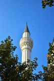 Islamic tower of a minaret. Of marble against a background of trees and a blue sky Stock Images