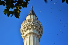 Islamic tower of a minaret of marble. Against a background of trees and a blue sky Stock Photos