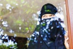Islamic woman looking at the window stock photo