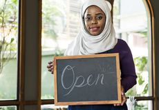 Islamic woman small business owner holding blackboard with smiling.  Royalty Free Stock Photos