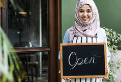 Islamic woman small business owner holding blackboard with smiling Royalty Free Stock Photo