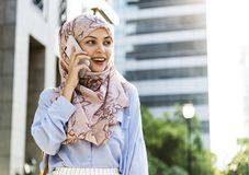 Islamic woman using mobile phone with smiling at building Stock Images