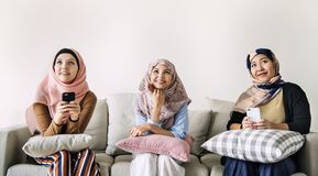 Islamic women friends using smart phone and looking up royalty free stock photos