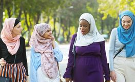 Islamic women friends walking and discussing together stock photography