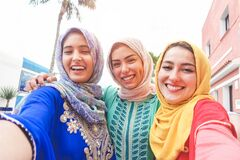 Islamic young friends taking selfie with smartphone camera outdoor - Happy arabian girls having fun with new trend technology -