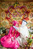 Islamische Hochzeit, Bräutigam, der eine Goldhalskette auf Braut setzt Traditi Lizenzfreies Stockfoto