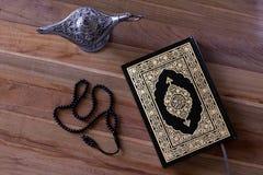 Islamisk bokQuran på woddenbrädet med en radband och en aladdinlampa - Ramadan/Eid Concept arkivbild