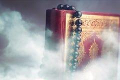 Islamski Książkowy Koran z różanem na popielatym tle Obraz Stock