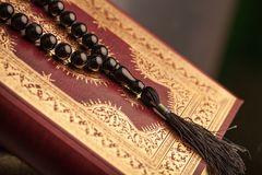 Islamski Książkowy Koran z różanem na popielatym tle Fotografia Stock