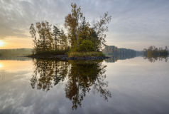 Island. A small island in a lake reflecting in the water Royalty Free Stock Photography