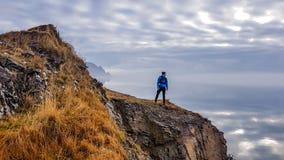 Island - anseende för ung man på klippan med en ändlös horisont arkivfoto