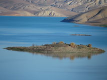 Island on artificial lake in Middle Atlas Mountains. Island on artificial lake in mountainside northern countryside in Middle Atlas Mountains landscape in Royalty Free Stock Images