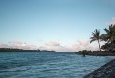 Island beach with palm trees and clouds over the horizon. View of island beach with palm trees and clouds over the horizon stock image