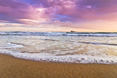 Island of Benidorm against purple sky and clouds. Seashore close up with view on island of Benidorm, Levante beach Stock Photos