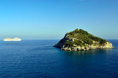 The island of Bergeggi and the cruise ship Costa C Royalty Free Stock Photos