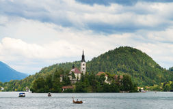 He island of Bled, Bled castle on cliff,  Julian Alps and Church of the Assumption, the front ground is stone and sea water, Bled Stock Images