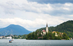 THe island of Bled, Bled castle on cliff,  Julian Alps and Church of the Assumption, the front ground is stone and sea water, Bled Royalty Free Stock Photography
