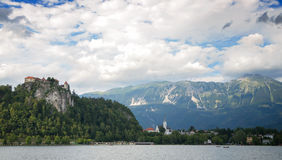 The island of Bled, Bled castle on cliff,  Julian Alps and Church of the Assumption, the front ground is stone and sea water, Bled Royalty Free Stock Photo