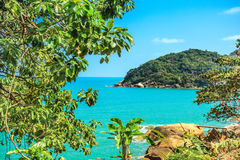 Island in blue ocean and green tropical trees Stock Images