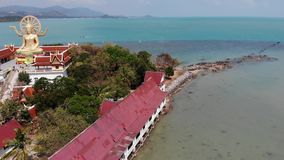 Island with Buddhist temple and many houses. Aerial view of island with Buddhist temple with statue Big Buddha. Surrounded by traditional houses on stilts in stock video footage