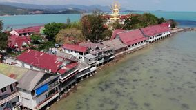 Island with Buddhist temple and many houses. Aerial view of island with Buddhist temple with statue Big Buddha. Surrounded by traditional houses on stilts in stock video