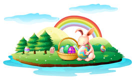 An island with a bunny and a basket of easter eggs Stock Photo